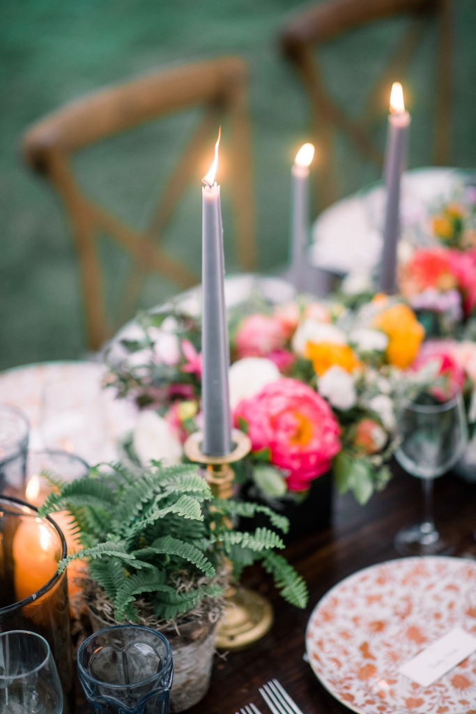 """We wanted the tablescape to be cohesive, but not too manicured,"" says planner Chloe Ewing. The result was an earthy mix of terra cotta, metallics, succulents, glowing votives, and blue taper candles—a nod to Jane's favorite hue. <i>Image by Timwill Photography</i>"