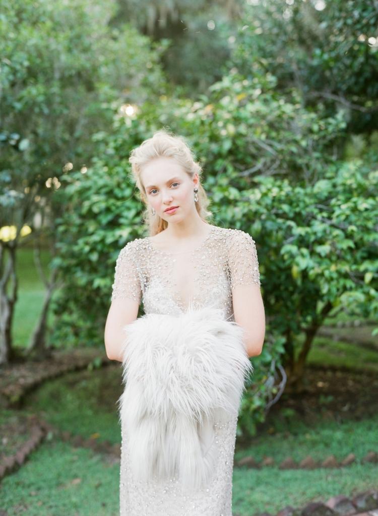 "Jenny Packham's  ""Jocasta"" beaded sheath dress with cap sleeves from White on Daniel Island. Elie Tahari's ""Carli"" faux fur jacket from Gwynn's of Mount Pleasant. David Yurman's ""Grisaille"" earrings from REEDS Jewelers. Photograph by Corbin Gurkin."