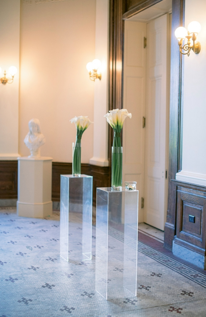 "Calla lily arrangements resting on Lucite pillars formed the ""altar.""   <i>Image Timwill Photography</i>"