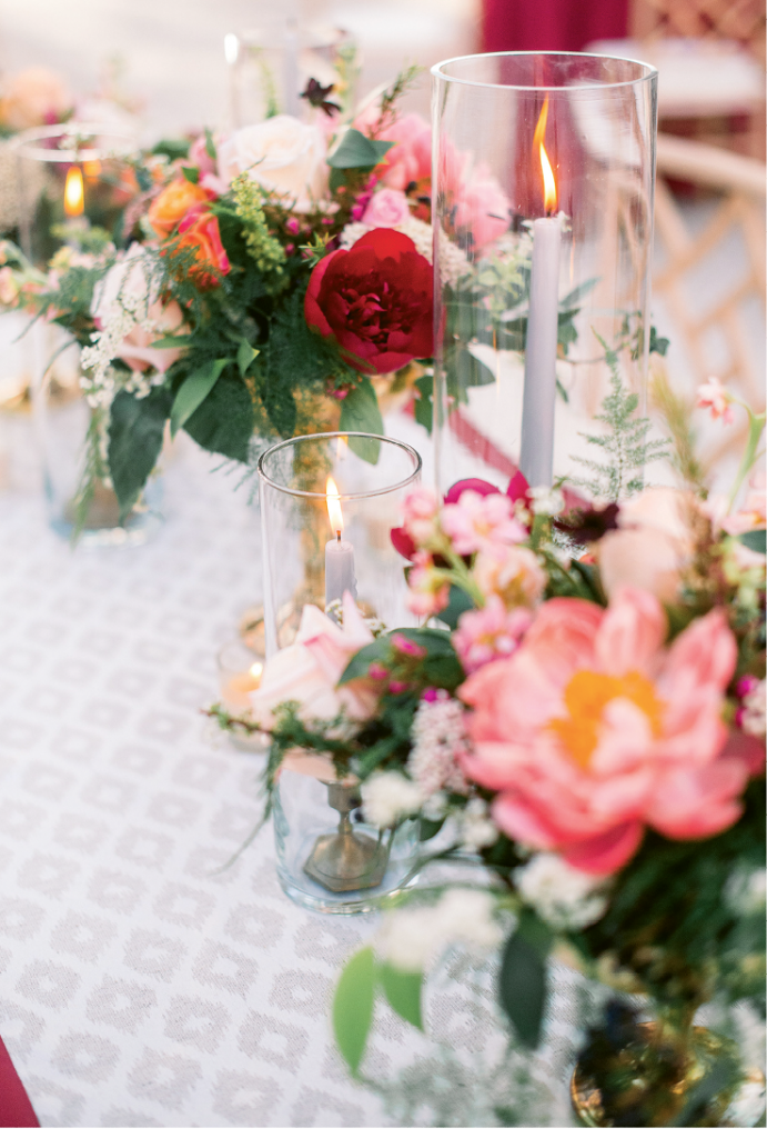 Roses, peonies, and viburnum berries sat atop table runners by the bride's company, The Social Spool.