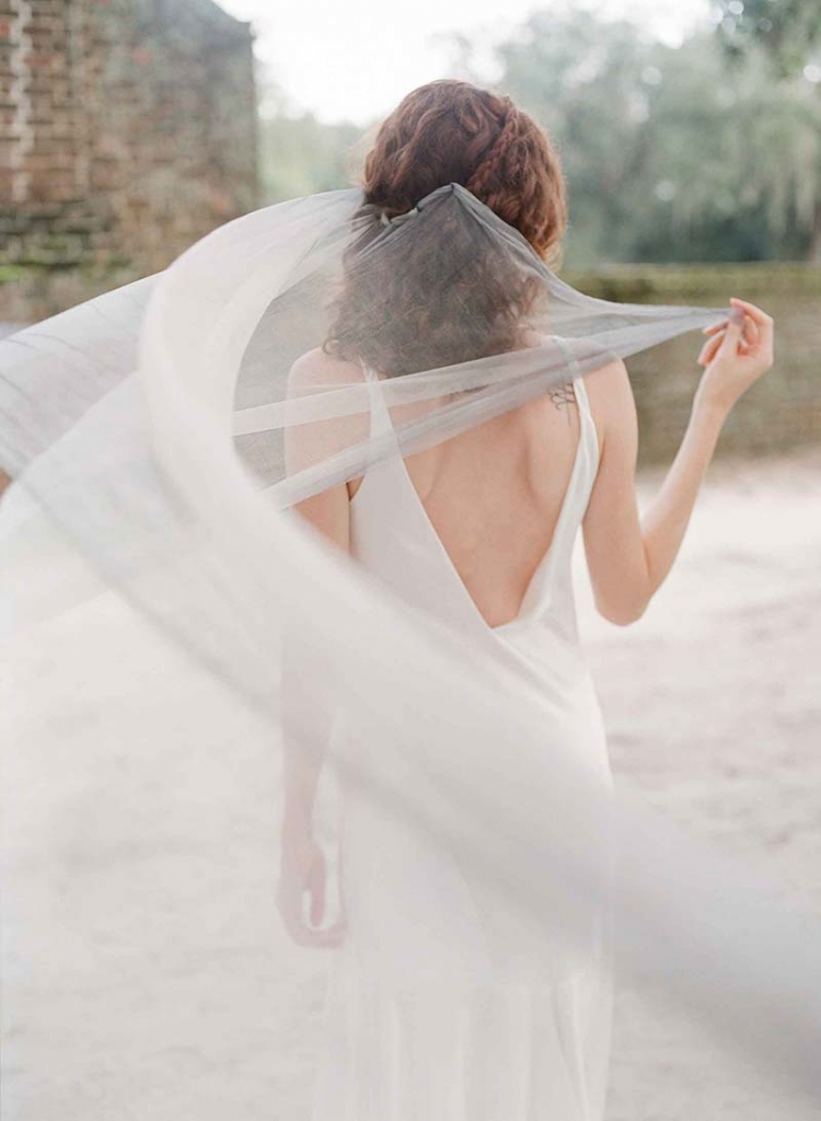 "Callie Tein's ""Bessette"" silk charmuese bias-cut gown  from Modern Trousseau flagship stores in Charleston,  Savannah, Nashville, and Louisville. ""Ursa"" halo from Emma  Katzka. Kirk Kara's diamond and sapphire ring from Diamonds Direct.   <i>Photograph by Corbin Gurkin</i>"