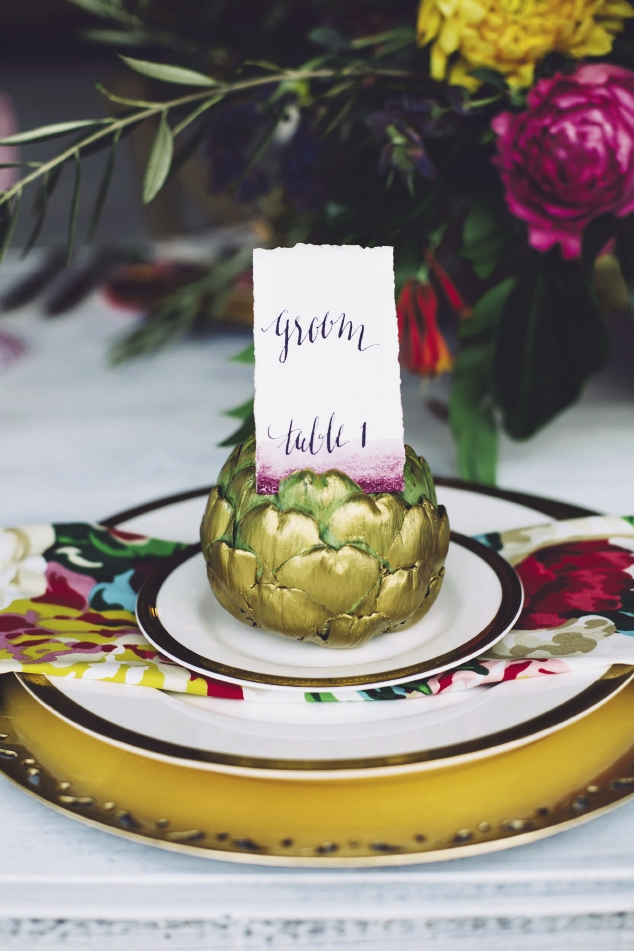 Produce makes a fanciful—and relatively inexpensive—placecard holder. Up the elegance with a wash of gold paint.  Watercolors by Britt Bates. Calligraphy by HR Deneau Paper Co. Signage by The Silver Starfish. Florals by Anna Bella Florals. Event design by Pure Luxe Bride. Image by Monika Gauthier Photography & Design.