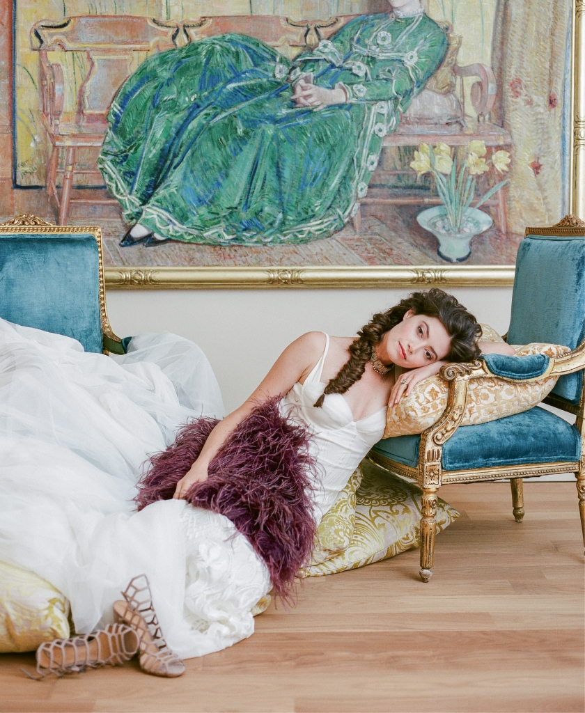 "Katie May's ""Geneva"" fitted silk embroidered gown with tulle train from Lovely. Jenny Packham's ""Santorini"" ostrich feather wrap in purple from RTW. Schutz's ""Jaden"" leather cage heels from Shoes on King. Pearl and turquoise gold choker from Out of Hand. Green amethyst and yellow gold ring from Gold Creations. Chairs and pillows from Ooh! Events. April  (The Green Gown) oil painting (1920) by  Childe Hassam. (Photo by Corbin Gurkin)"