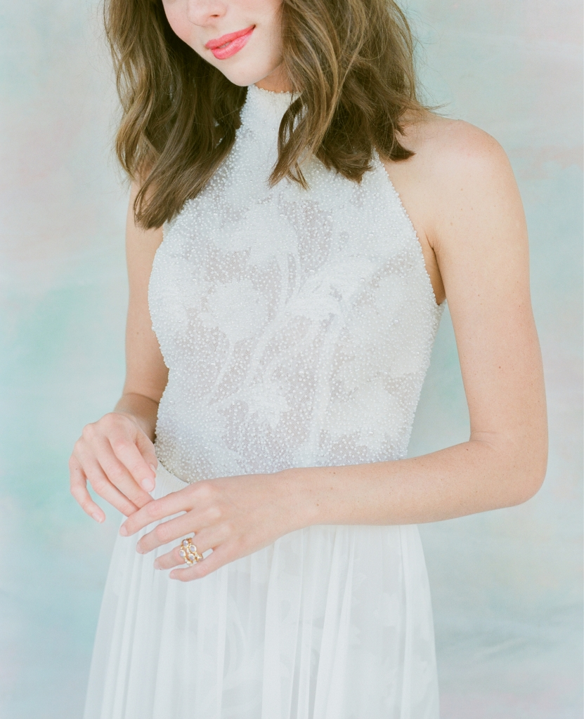 "Limor Rosen's ""Jade""  leaf-embroidered lace gown with beaded halter top and chiffon skirt from  Lovely Bride. Mazza's moonstone, diamond, and gold stacked ring from Croghan's Jewel Box. Hand-painted backdrop by Anne Girault of  Boutique Tents.   <i>Photograph Corbin Gurkin</i>"