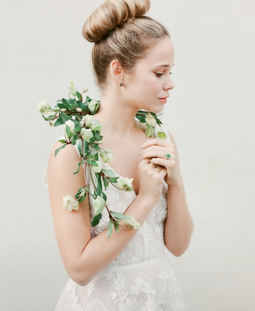 "Lela Rose's ""The Vineyard"" silk embroidered floral gown from Maddison Row. 14K yellow gold  labradorite and opal  earrings from Paulo Geiss Jewelers. 14K white gold, emerald, and diamond estate ring from Croghan's Jewel Box. Hellebore  garland by Gathering Floral + Event Design."