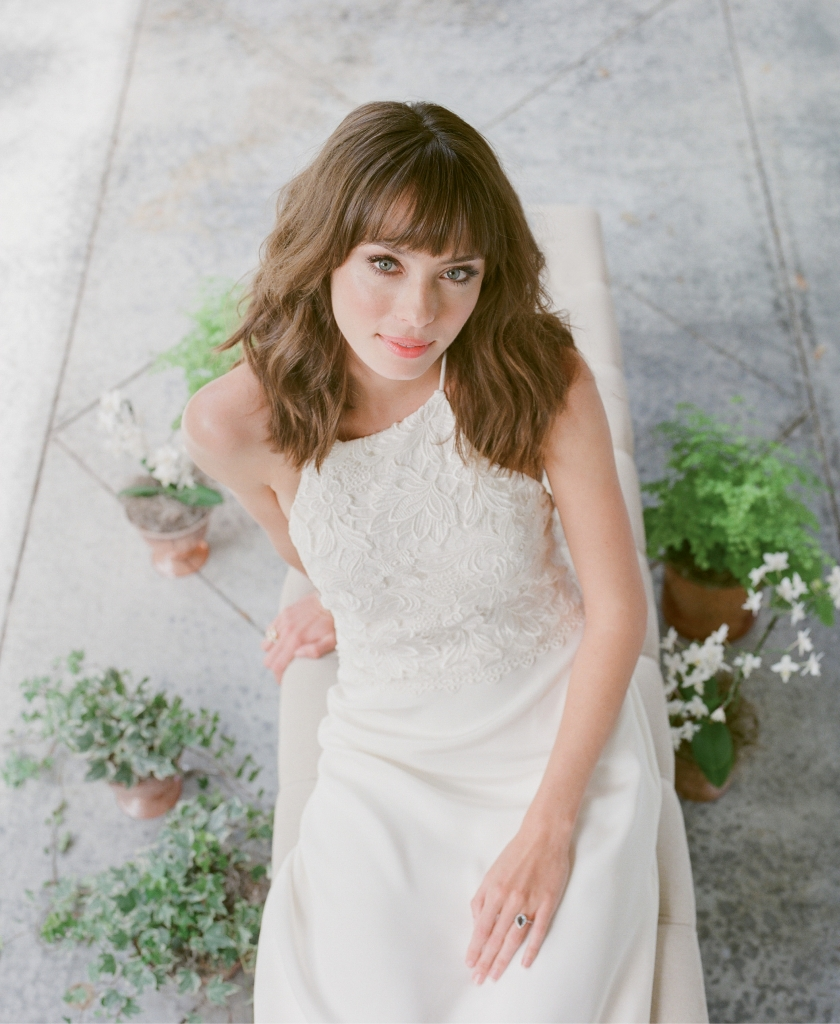 "Katherine McDonald's ""Kipling"" Guipure  lace and silk crepe  gown from Kate  McDonald Bridal  (also available through  Lovely Bride). Royal Jewelry's blue topaz  and gold ring from Diamonds Direct.  Bench from Snyder Events. Plants from Roadside Blooms.   <i>Photograph Corbin Gurkin</i>"