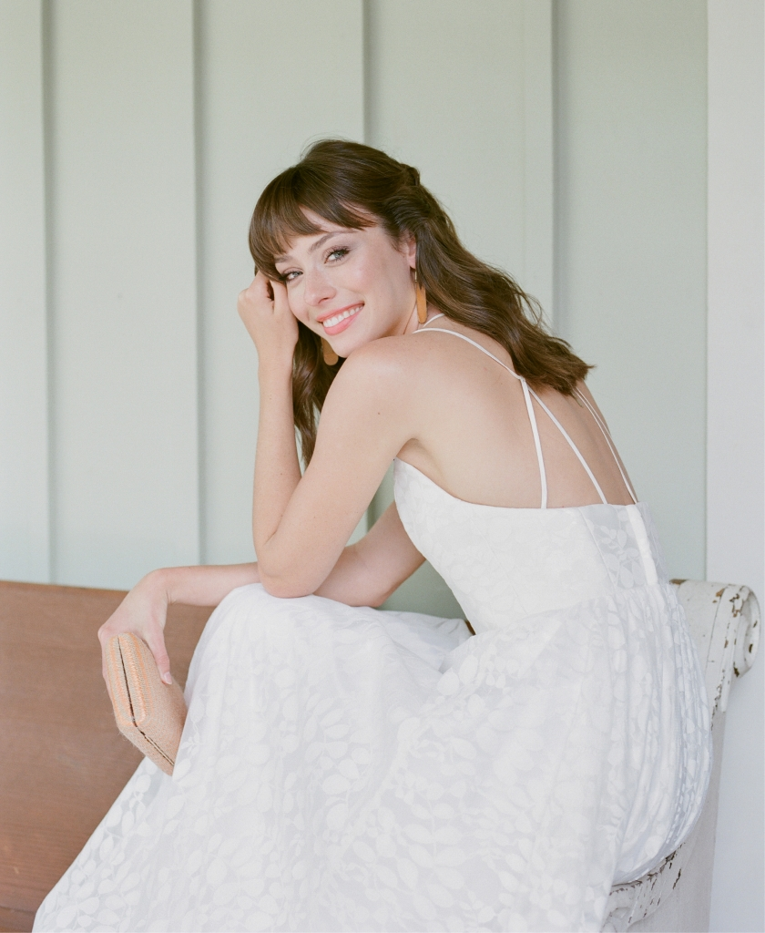 "Truvelle's ""Hamilton"" lace gown with crisscross straps from Bridal House of Charleston. Meyelo's ""Oba""  brass earrings  from Celadon. Inge Christopher clutch  from Shoes on King.   <i>Photograph Corbin Gurkin</i>"