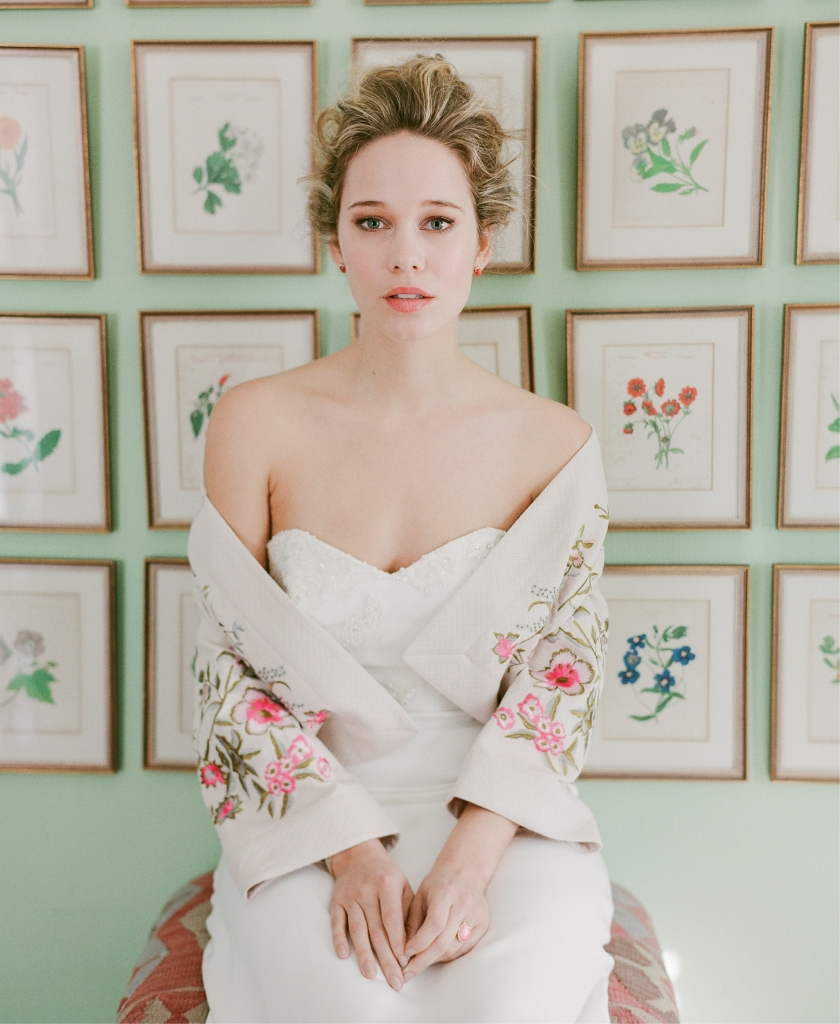 "Katherine McDonald's ""Banks"" gown from Kate McDonald Bridal. Darling London's ""Hayden"" embroidered jacket from Out of Hand. Sea + Stone's 14K yellow gold, coral, and diamond earrings from Kiawah Fine Jewelry. Robert Coin's 18K rose gold, pink agate, and diamond ring from Paulo Geiss Jewelers."