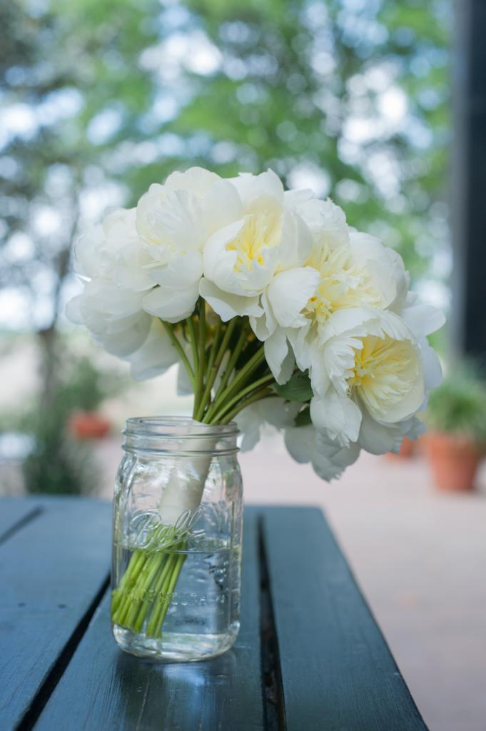 WHAT A HANDFUL: Stems arranged a simple white peony bridal bouquet to complement D'Anne's gown.