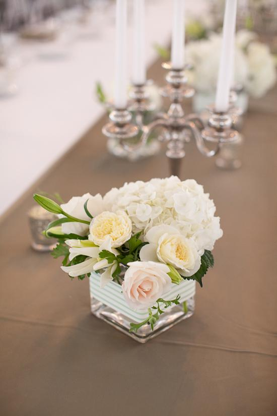 SET THE TABLE: Placed between vases brimming with pale posies, candelabras cast a glow over tabletops as guests dined.