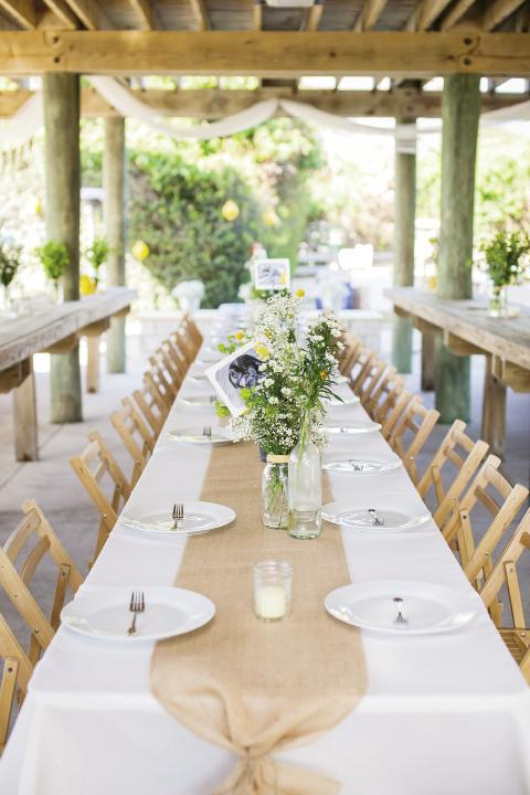 FÊte Set: Reception tables from Snyder Event  Rentals were kept simple with a burlap runner and a rustic arrangement of flowers. For table numbers, the couple printed numerals on photos of their dogs and tucked them into the flower arrangements.