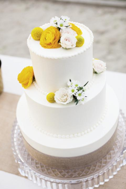 Piece of Cake: The Cake Stand made the classic carrot and vanilla cake, which the bride dressed up with fresh flowers and a burlap-wrapped stand.