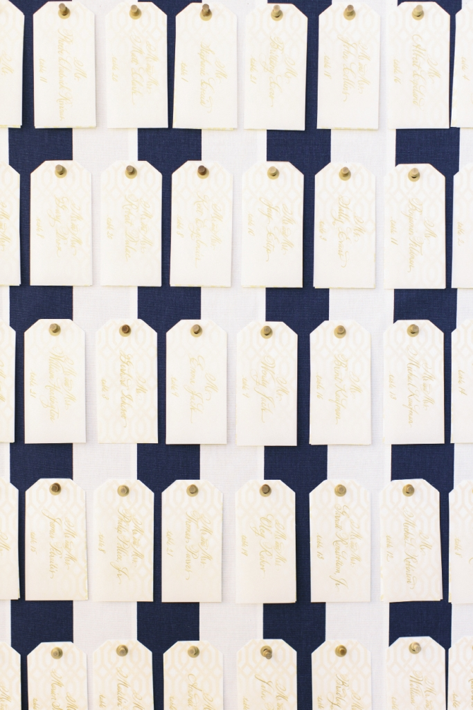 Posted with wooden thumbtacks, paper luggage tags sporting the same pattern as the wedding's reply card were  calligraphed to direct guests to their tables.