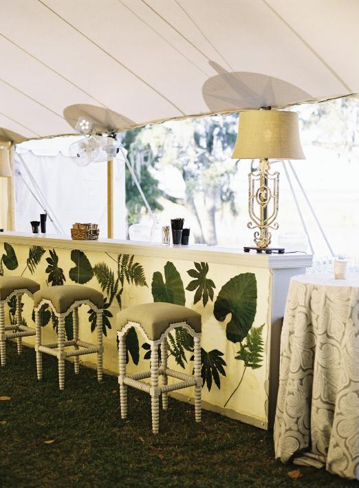 For a stunning and singular bar setup in keeping with the wedding's aesthetic, planner Calder Clark affixed fern, fatsia, and elephant ear leaves to linen fabric, then pressed them behind a glass front. Custom bar by Blossom Events. Bar stools and lamps by Calder Clark. Linens by La Tavola. Tent by Sperry Tents Southeast. Photograph by Tec Petaja.