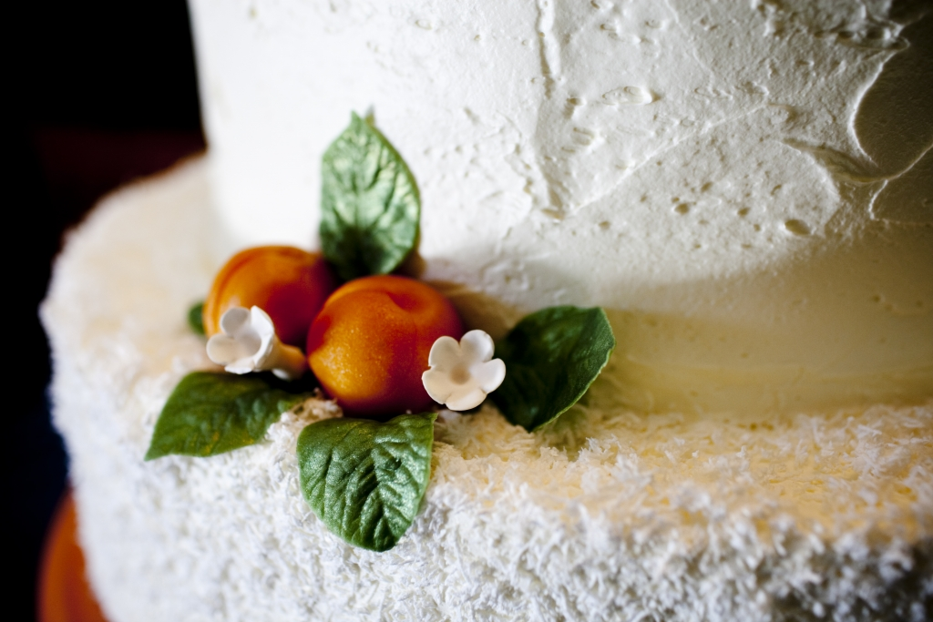 "COLOR-CODED CONFECTION: In keeping with the wedding's ""apricot and azure"" theme, the traditional white butter cake, made by Wedding Cakes by Jim Smeal, was garnished with marzipan apricots. The wooden cake stand was painted to match the pantone shade of the theme, as well."