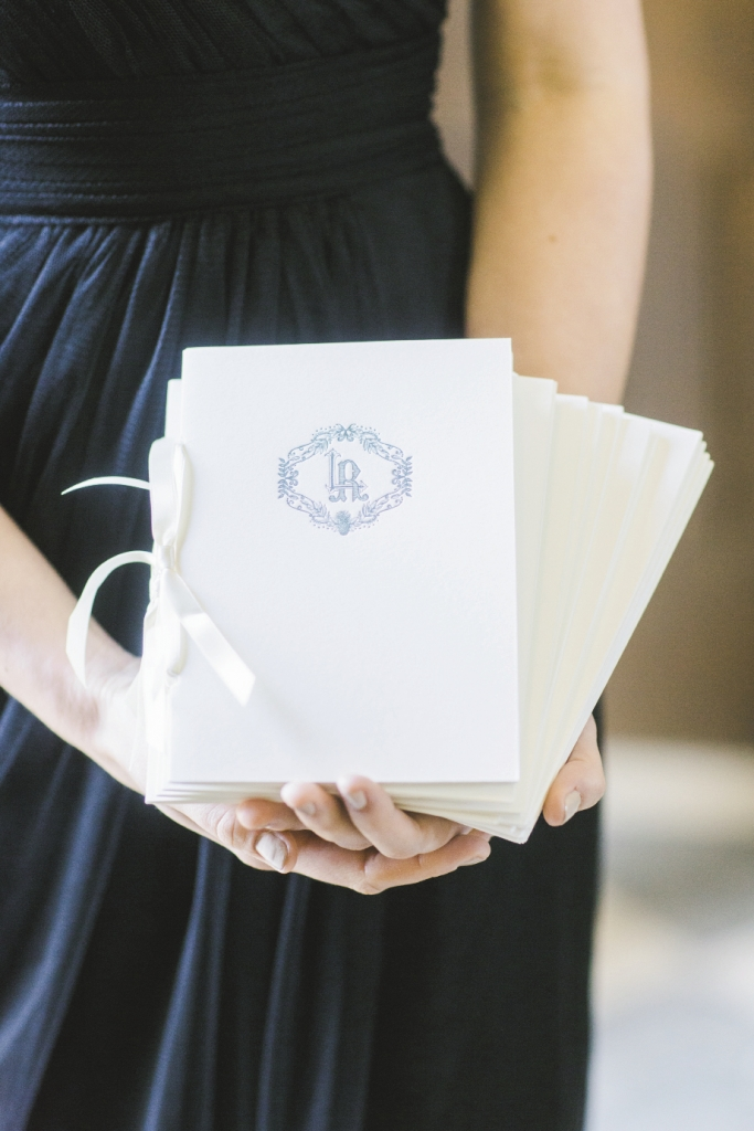 His-and-her monograms topped letterpressed program booklets that were finished with ribbon. Stationery by Ceci New York. Image by Elisabeth Millay Photography.