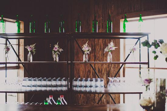 BOTTLE SERVICE: Emerald wine bottles and rose arrangements accented the bar.
