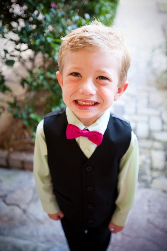 WELL SUITED: Matching the floral color palette, the ring bearer sported a fuchsia bowtie and cheery smile.