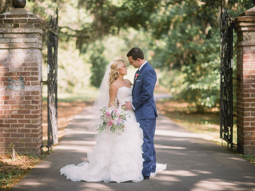Gown by Allure Bridals. Hair and makeup by Paper Dolls. Tux by Stephen Geoffrey and from M. Dumas & Sons. Florals by Branch Design Studio. Image by Timwill Photography at the Legare Waring House.