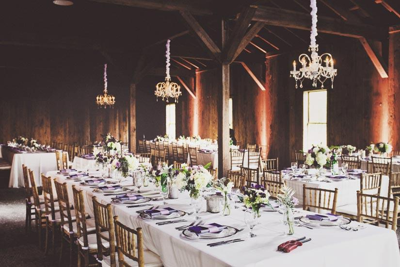 AMETHYST LUXURY: Emerald green wine bottles placed next to centerpieces of maidenhair fern, roses, raspberries, sweet peas, and thistle and chandeliers from Technical Event Company upped  the romance factor in the rustic Cotton Dock.