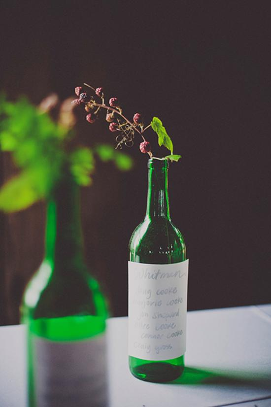 MESSAGE ON A BOTTLE: Green wine bottles, topped with raspberry branches and adorned with handwritten quotes from the couple's favorite authors, served as table numbers.