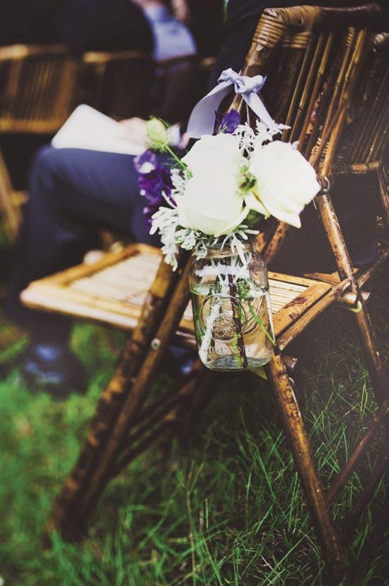 HANG ON: Mason jars hung with lavender ribbon and filled with white roses, silver-green dusty miller, and purple delphinium graced the ceremony aisle.