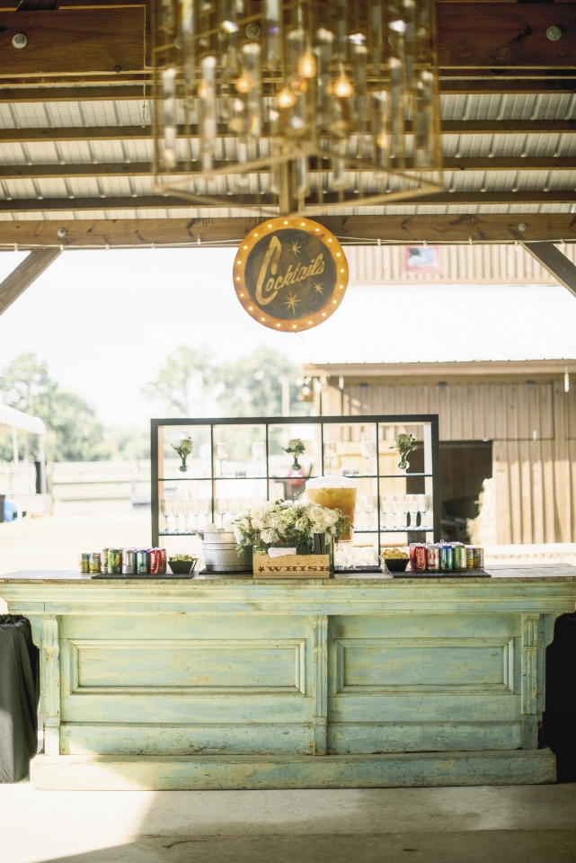 Specialty décor (like an Edison-bulb sign and wooden bar) gave depth, character, and color to the wedding's chiefly neutral palette. The clue you've picked the right rentals? They look indigenous to your location.