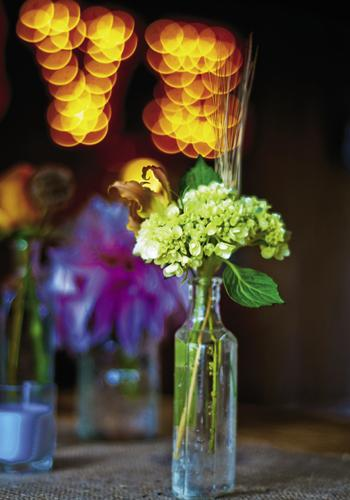 GO GREEN: Vintage soda and tincture bottles served as vases to hold stems of green hydrangeas and persimmon-colored lilies.