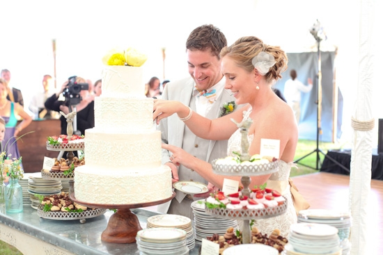 EASY ACCESSORIES: The couple's four-tiered, white patterned confection from Magnolia Wedding Cakes was crowned with two yellow peonies and stood atop a simple but sturdy wooden stand.