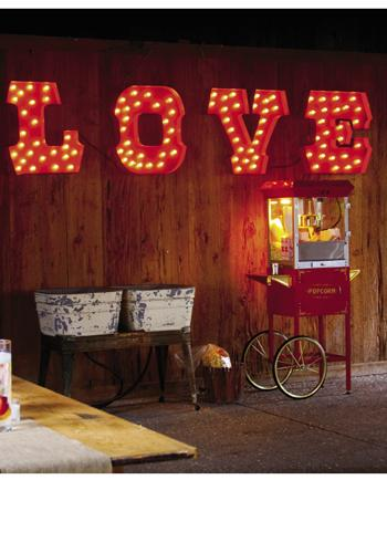 "PING QUEEN: Mary rented most of her décor, like a  vintage popcorn machine, from Ooh! Events. Perhaps her favorite score? The red, lighted ""LOVE"" sign, which was a surprise donated element from the gals at Ooh! Events."
