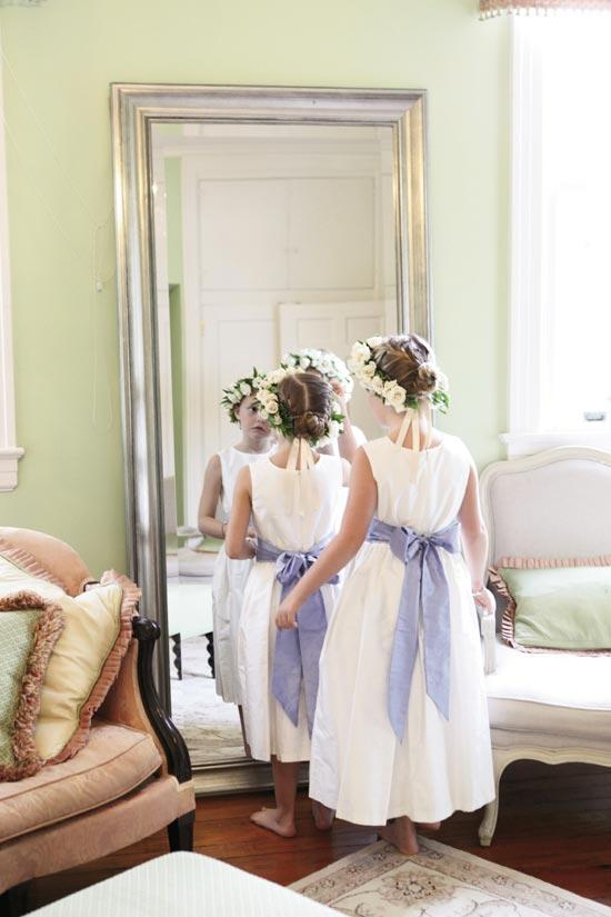 LADIES IN WAITING: Flower girls donned blush floral wreaths and cornflower silk sashes.