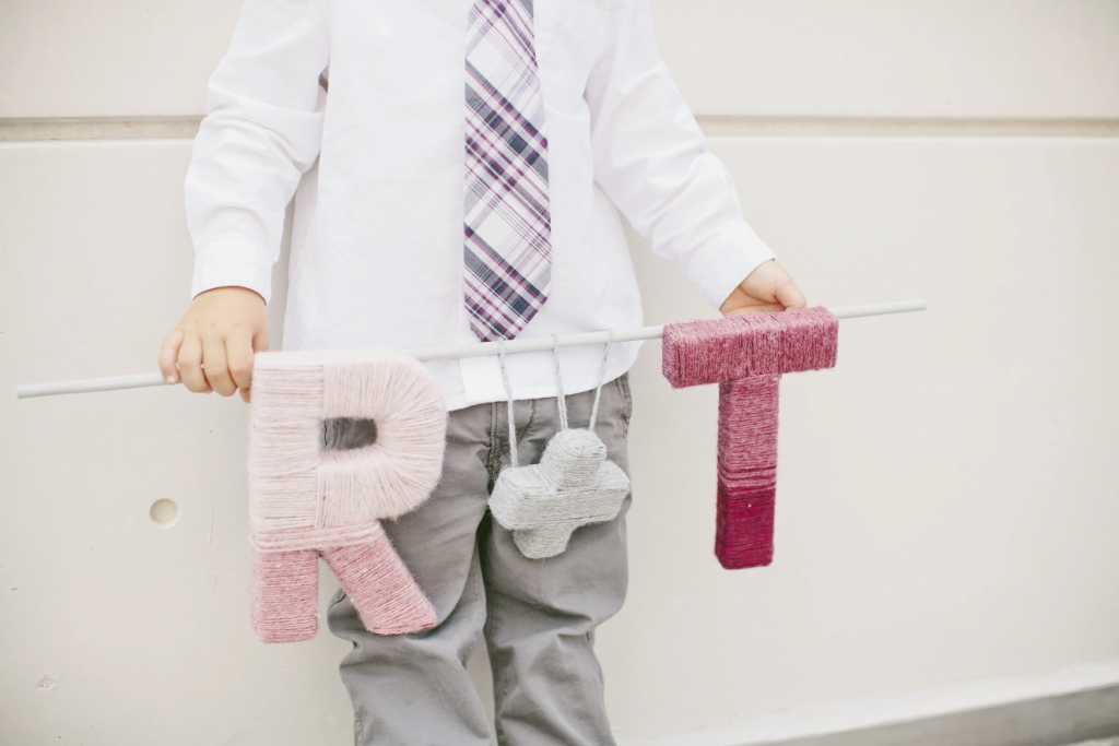 "INITIAL INTRODUCTION: Thomas' nephew carried an ""R + T"" banner made from yarn wound around cardboard letters."