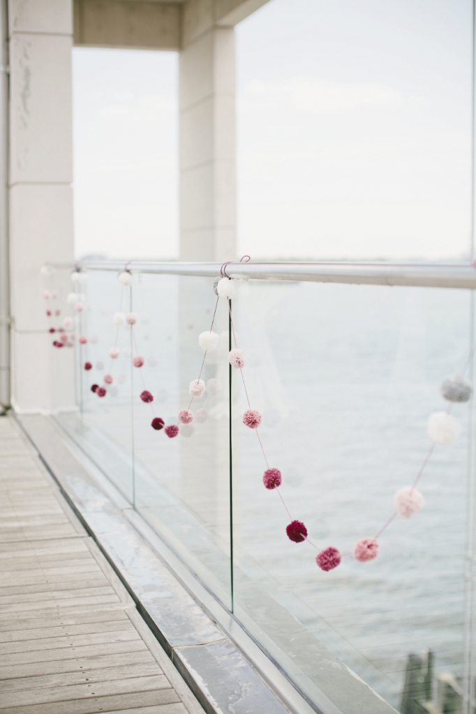 DELICATE CONTRAST: Pom-pom garlands hung along the balcony for subtle punctuations of color.