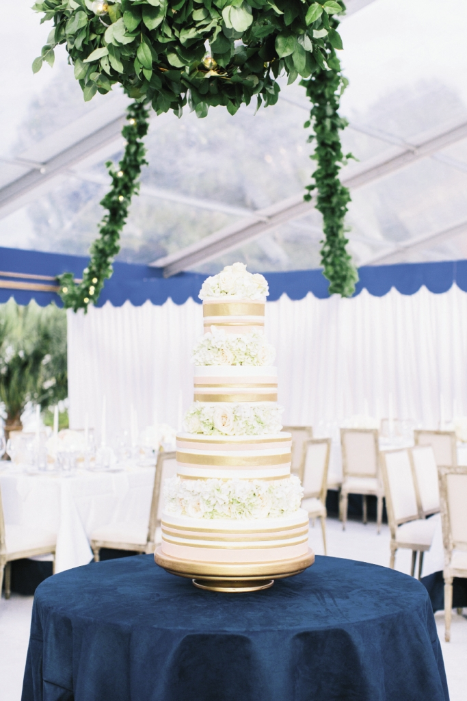 Perched atop a table covered in the same sueded navy fabric that trimmed the other linens, the dessert from Wedding Cakes by Jim Smeal wore fondant ribbons of gold and pink.