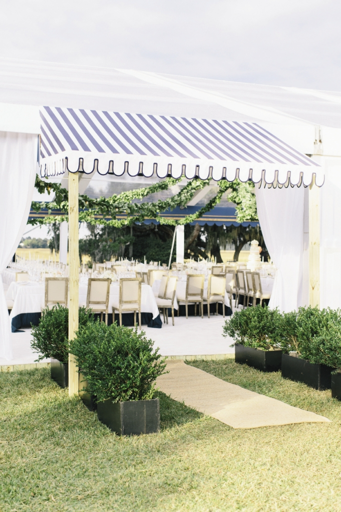 "Reception tent entrances were made formal with custom-made fabric awnings and boxwood ""hedges."""