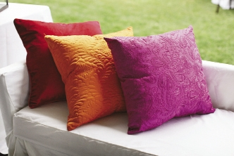 GET COZY: Adding color (and comfort), citrus- and berry-toned pillows lined benches.