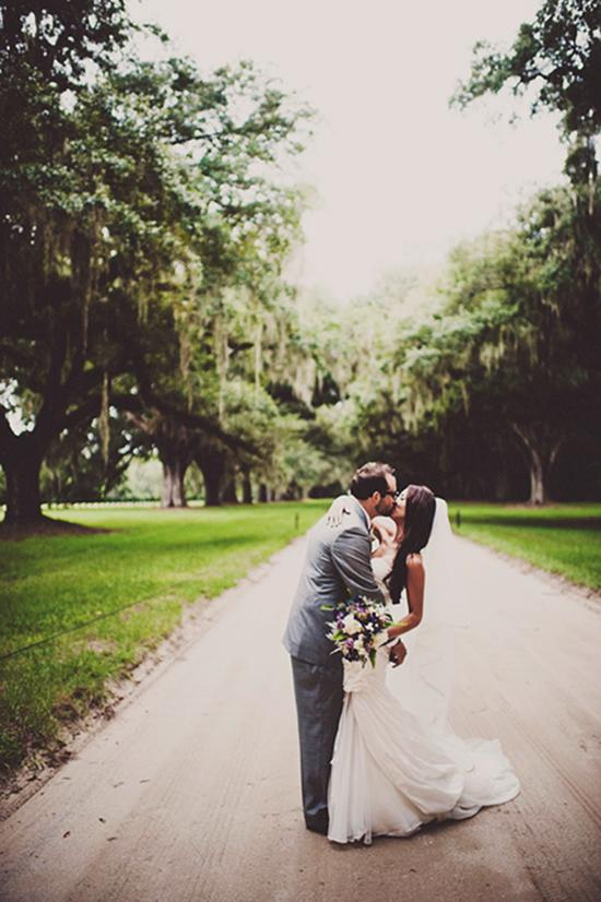 ALL YOU NEED IS LOVE: The newlyweds kissed for the camera on the oak-lined dirt drive of Boone Hall Plantation.