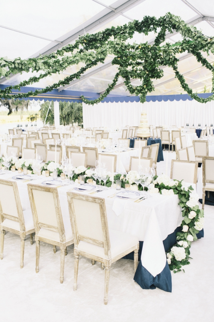 To transform the open-air tent into a black-tie reception hall, Tara and her team laid down cream-colored carpet, hung garlands of fresh greens braided with twinkling lights, and draped tables in custom floor-length linens. The head table was marked with a verdant 29-foot floral runner.