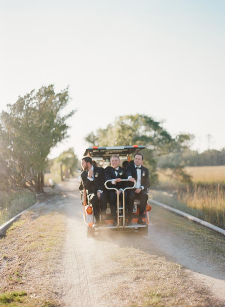 The groomsmen, along with 350 other guests, were shuttled by golf carts over a single-lane bridge to the secluded ceremony site.