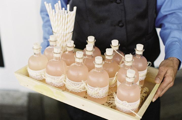 SIGNATURE SIP: Soirée filled small corked glass bottles with pink Lowcountry Lemonade (made with peach schnapps), tied them off with lace, and served each with a striped straw.