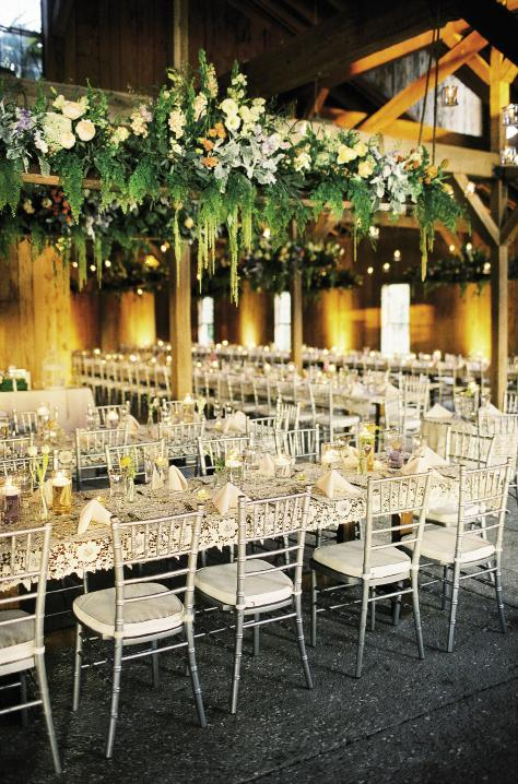 NEW HEIGHTS: Julie adorned the Cotton Dock's wooden rafters with flowers from A Victorian Flower Dictionary, which gives each bloom a unique meaning. Peach-hued peonies symbolize a happy marriage while yellow roses are for contentment. The ferns and Spanish moss served as a nod to the Lowcountry.