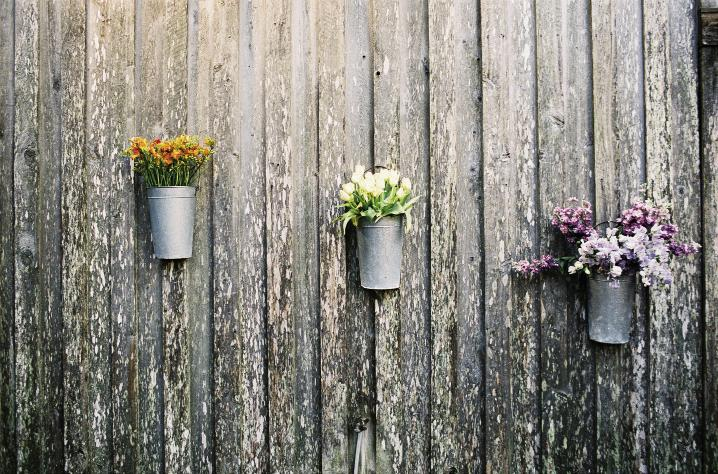 HANGING AROUND: Friend-turned-planner Julie Righetti hung French market buckets stocked with clusters of like blooms—tulips, alstroemeria, and spray roses—along the Cotton Dock's exterior walls.