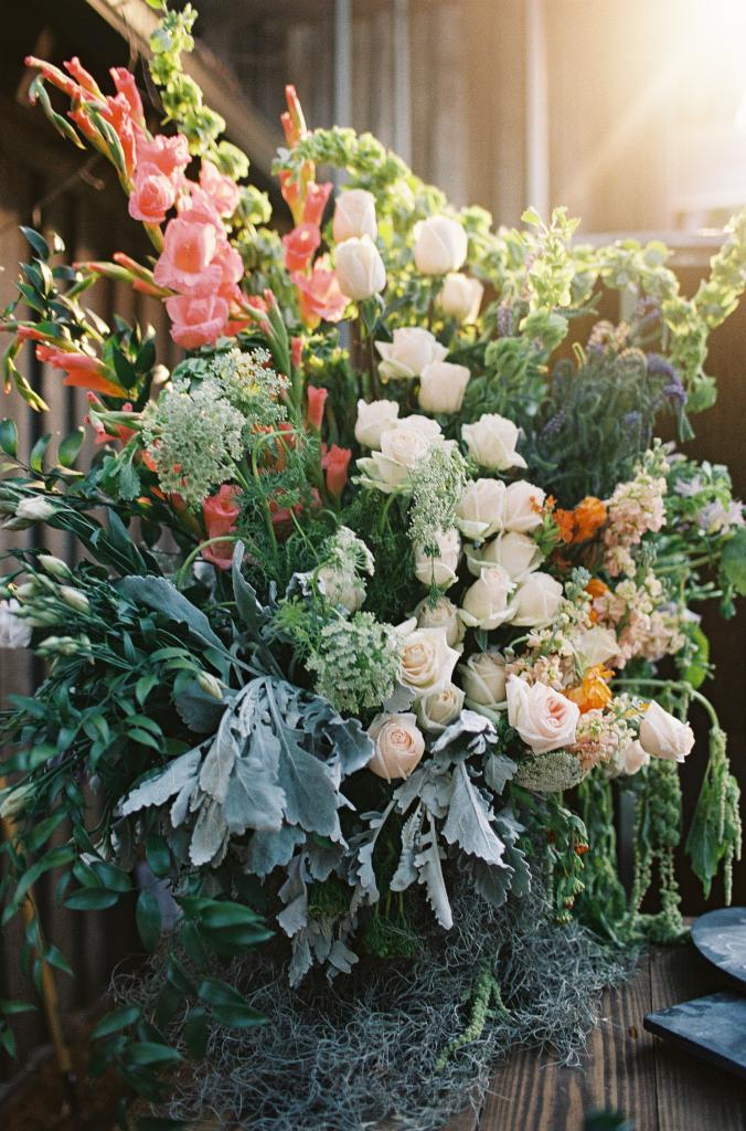 "FLORABUNDANCE: ""I wanted a lot of flowers, but I wanted all the flowers to have meaning. I used the Victorian flower dictionary and my coral, creams, and lilac colors to carefully choose all the flowers in my bouquet and in the centerpieces,"" says Mary Jo."