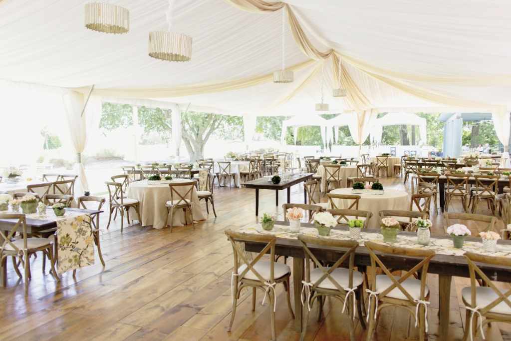 LUXE LIFE: The dining hall tent, with its honey-toned wooden floors, mercury-glass drum shades, and gently gathered fabric draping, was an oasis of elegance in the open field.