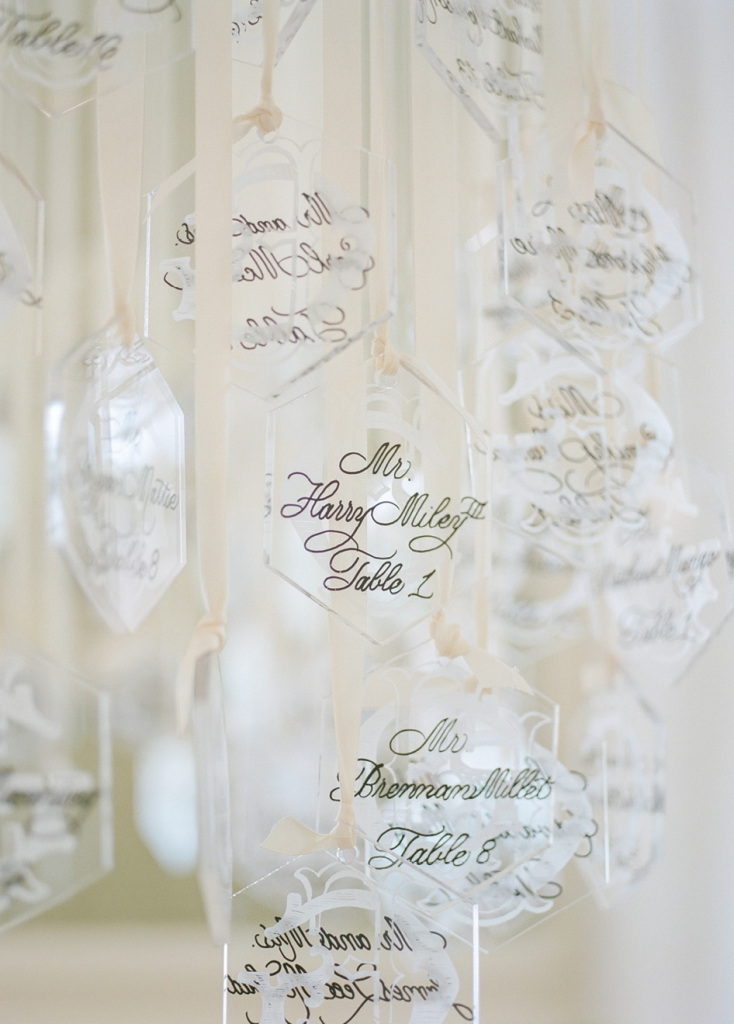 To pump up visual interest, Tara contrasted elements; here, Lucite ornaments (appropriate to the winter season) engraved with the couple's initials and calligraphed with guest names and table numbers were hung with double-faced satin ribbon.   <i>Photograph by Corbin Gurkin</i>