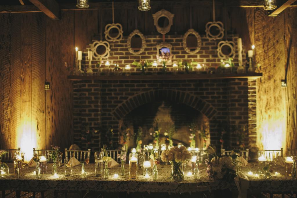 SIMPLE TOUCHES: The location's rustic beauty was aglow with myriad candles. The hearth was filled with a gentry of tall flowers, while white-framed mirrors hung above the mantel.