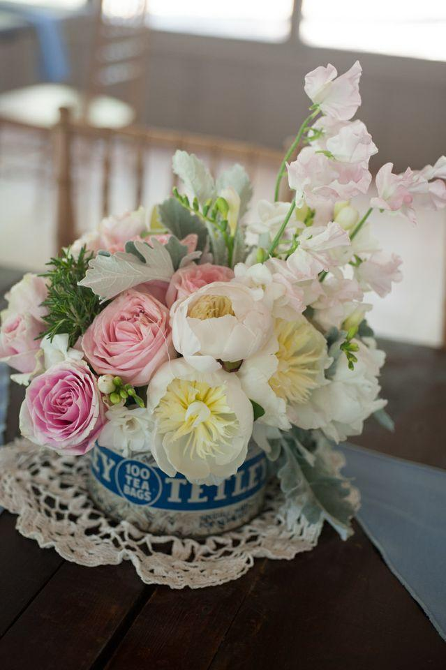 PRECIOUS METAL: For vintage-inspired centerpieces, blush bouquets of roses, peonies, carnations, and rosemary were tucked into old-fashioned tea-tins and set atop lace doilies.