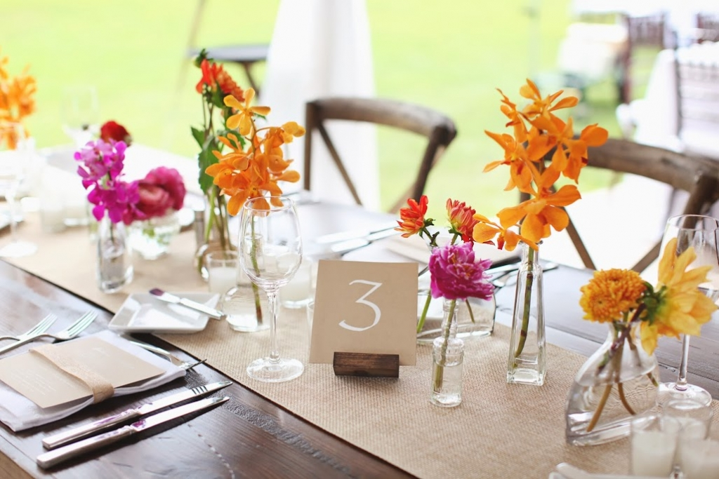 SIMPLE TOUCHES: Table numbers penned onto kraft paper matched the look of dinner menus, while flowers were tucked into clear vessels of varying shapes and sizes.