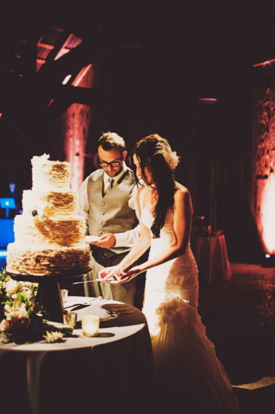 ALL ABOUT THE OMBRE: Once the sun had set, the couple cut into their ombre-ruffled wedding cake.