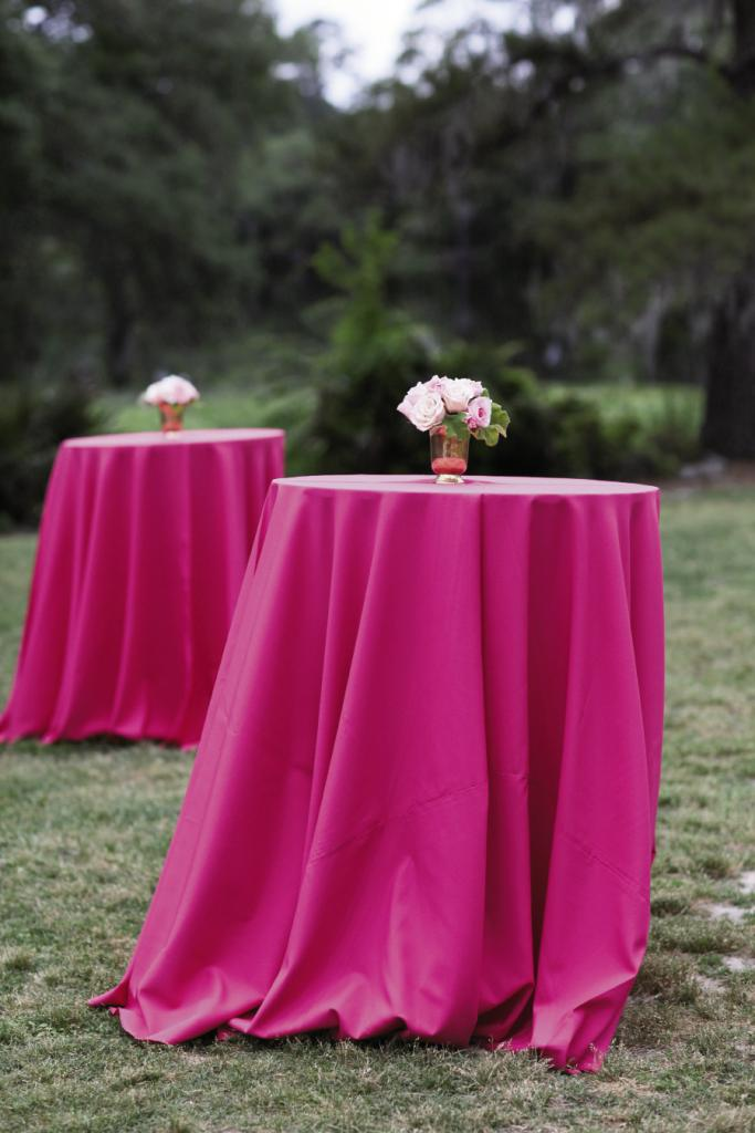 TOP THIS: High-top tables draped in fuchsia linens invited mingling and gave rich contrast to the lush green grounds.